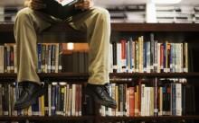 Мужчина в библиотеке читает книги