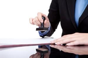 Девушка ставит печать на документ