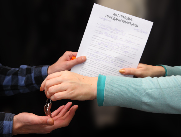 Женщина передает акт-приема передачи и ключи от квартиры