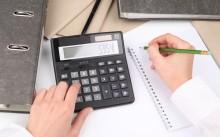 Мужчина вычисляет стоимость на калькуляторе