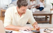 Мужчина рассчитывает долги на калькуляторе