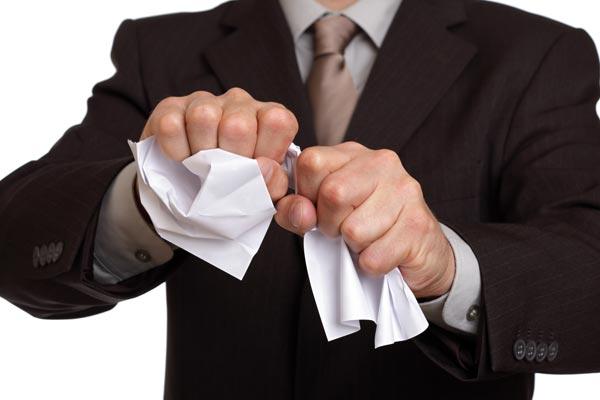 Мужчина мнет бумагу