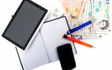 Ручка, блокнот, планшет и деньги на рабочем столе